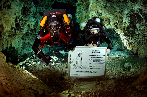 Two highly experienced rebreather divers approach the Grim Reaper sign at Ginnie Springs inside Devil's Ear Spring. These signs are meant to warn untrained divers about the hazards of diving in underwater caves.